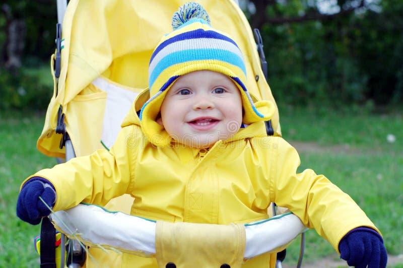 婴儿车的微笑的婴孩 免版税库存照片