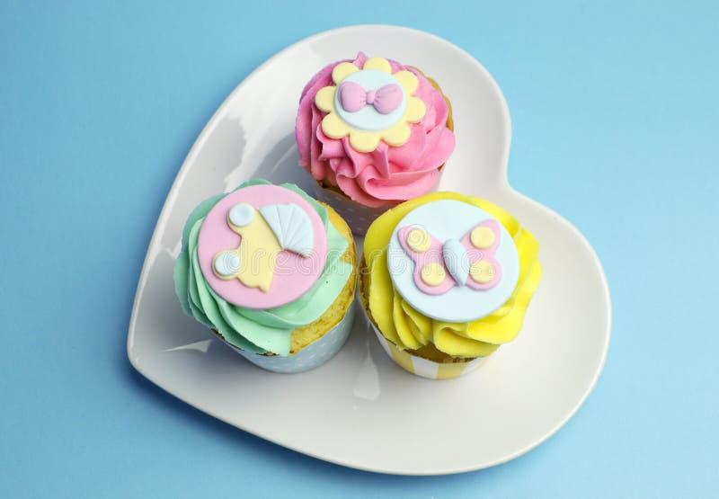 婴儿送礼会或儿童的桃红色、水色&黄色杯形蛋糕-天线 免版税库存图片