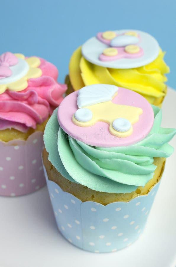 婴儿送礼会或儿童的桃红色、水色&黄色杯形蛋糕-接近的摇篮车 免版税图库摄影