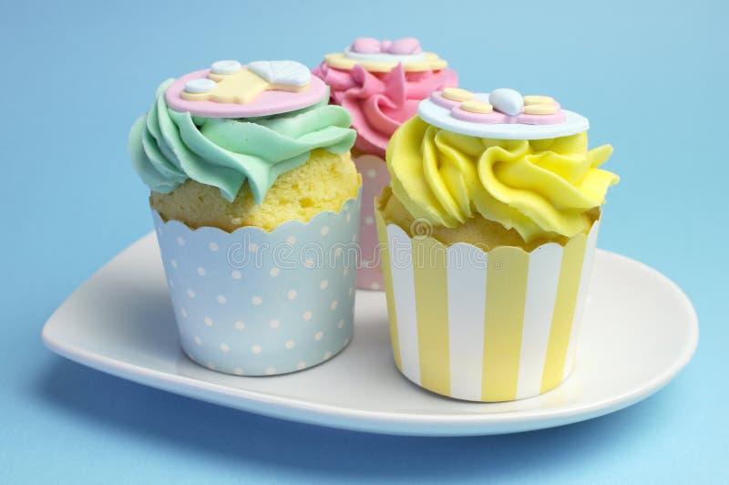 婴儿送礼会或儿童的桃红色、水色&黄色杯形蛋糕 库存图片
