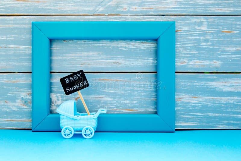 婴儿送礼会-戏弄有蓝球板标志的摇篮车与蓝色框架和木背景 免版税库存图片