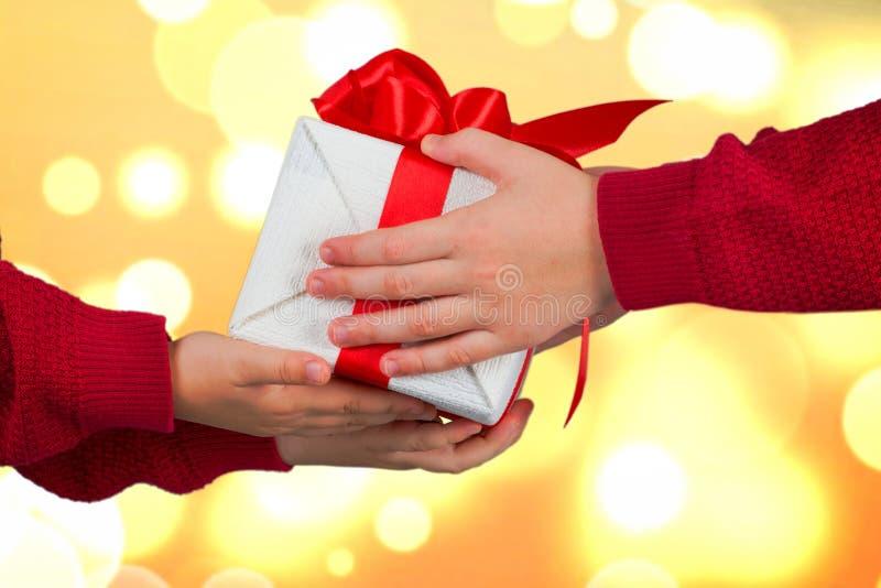 兄弟交换圣诞礼物 孩子的手有礼物的 圣诞快乐和节日快乐! 图库摄影