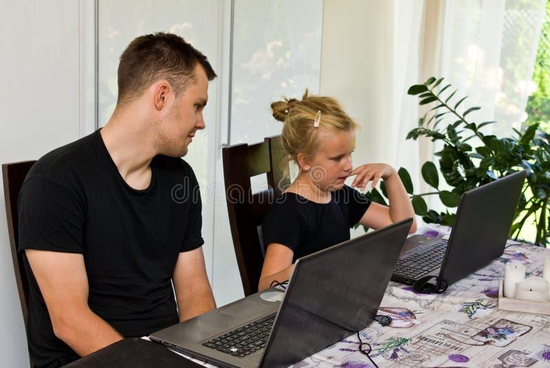 兄弟和姐妹与便携式计算机一起 库存图片