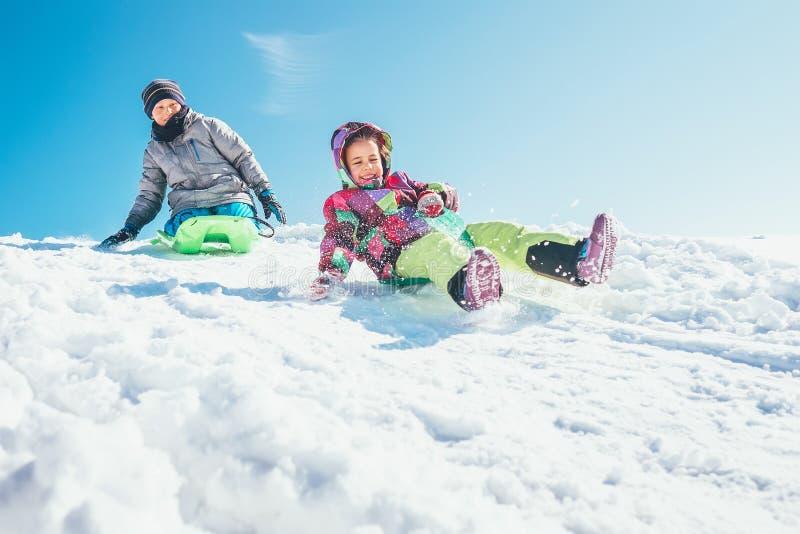 兄弟和姐妹从雪倾斜滑下来 冬时p 免版税库存图片