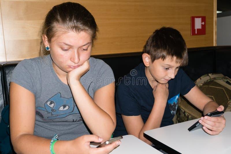 兄弟和姐妹使用与等待的智能手机吃午餐 免版税库存照片