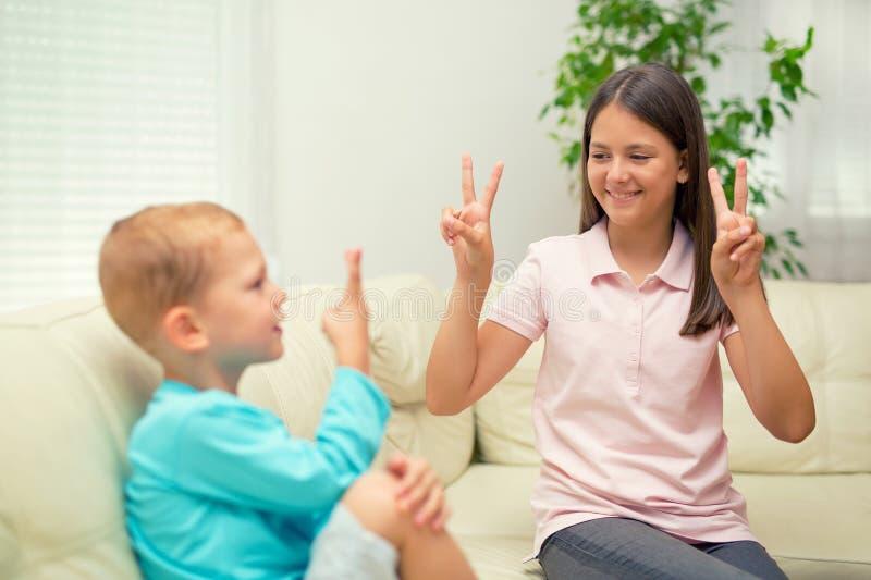 兄弟和姐妹在家学会手势语 库存图片