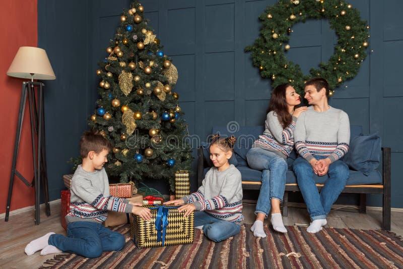 兄弟和姐妹在新年树附近考虑有礼物的一个大箱子在屋子里,并且父母坐沙发 图库摄影