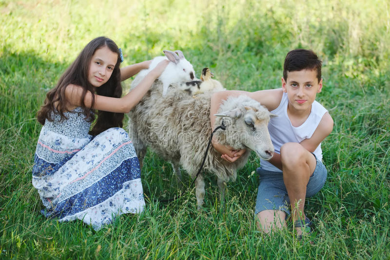 兄弟和姐妹在村庄度过夏天 免版税库存照片