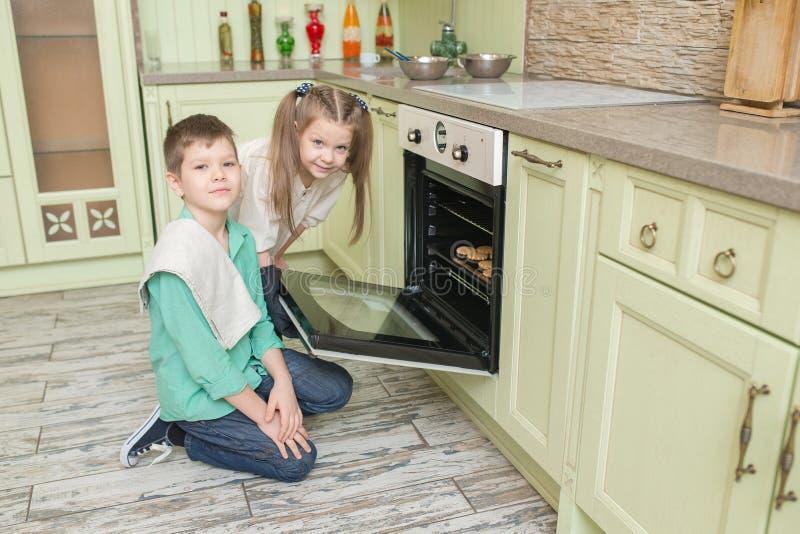 兄弟和姐妹在烤箱的烘烤曲奇饼在厨房里 库存照片