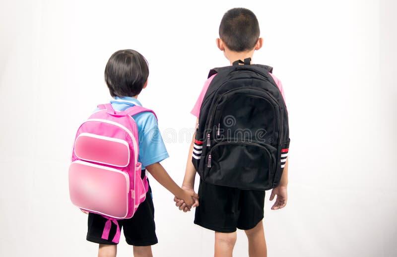 兄弟和姐妹在白色背景的藏品背包 免版税库存图片