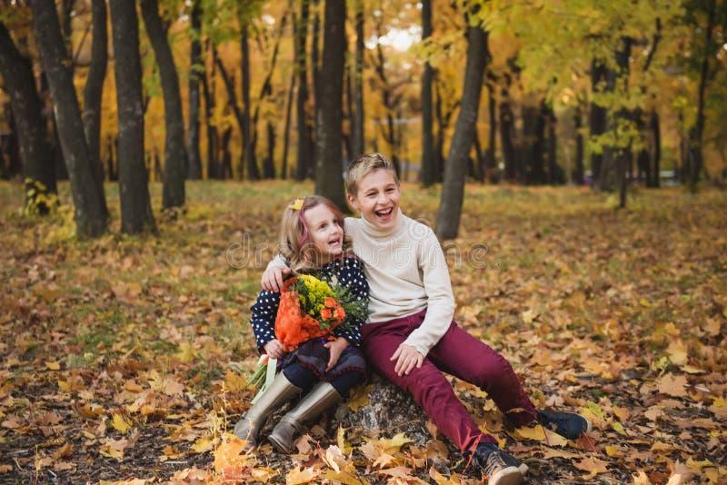 兄弟和姐妹在秋天公园 儿童笑 免版税库存图片