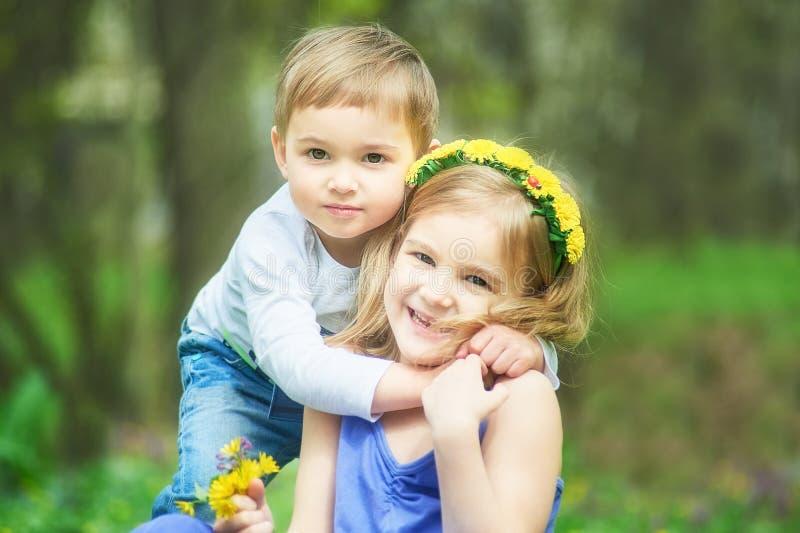 兄弟和姐妹坐草 儿童的比赛,休闲 两个孩子坐绿色草甸和微笑 r 免版税库存照片