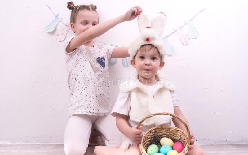 兄弟和姐妹庆祝复活节 男孩在兔子服装打扮并且举行一korunzku用复活节彩蛋 免版税库存图片