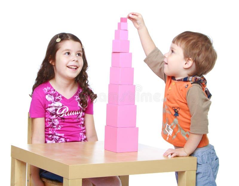 兄弟和姐妹收集在的红色金字塔 免版税库存图片