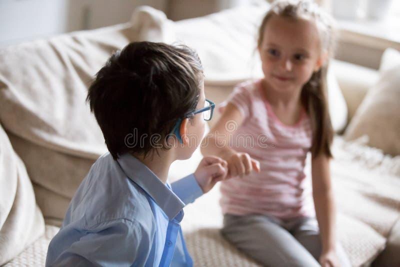 兄弟和姐妹紧压小指作为和解的标志 库存照片