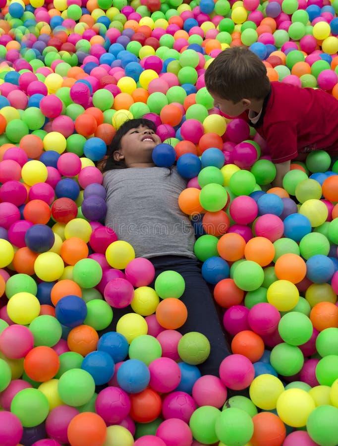 兄弟在多彩多姿的小球大堆放置  图库摄影