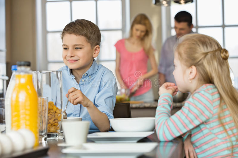 兄弟姐妹吃早餐在与烹调的父母的桌上在背景 免版税图库摄影