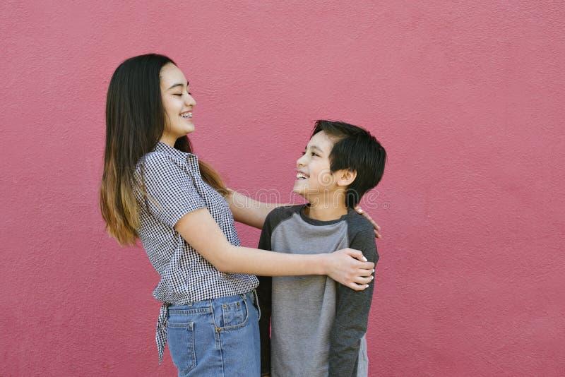 兄弟姐妹有拥抱和笑互相兄弟和姐妹乐趣的富感情的片刻 库存图片
