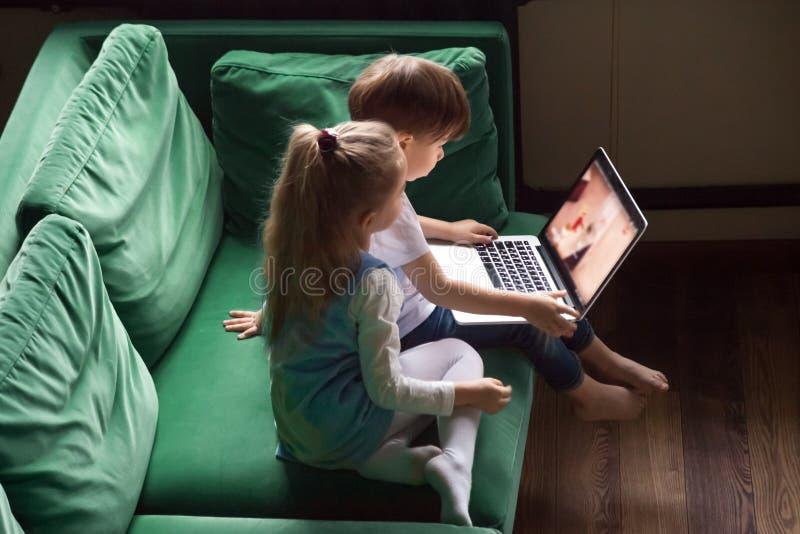 兄弟姐妹男孩和使用膝上型计算机togethe的女孩观看的孩子动画片 免版税库存照片