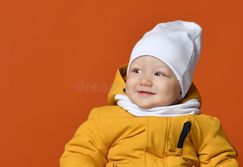 兄弟子项给愉快的一个姐妹微笑的二冬天穿衣 在下来夹克的孩子 方式子项 免版税图库摄影