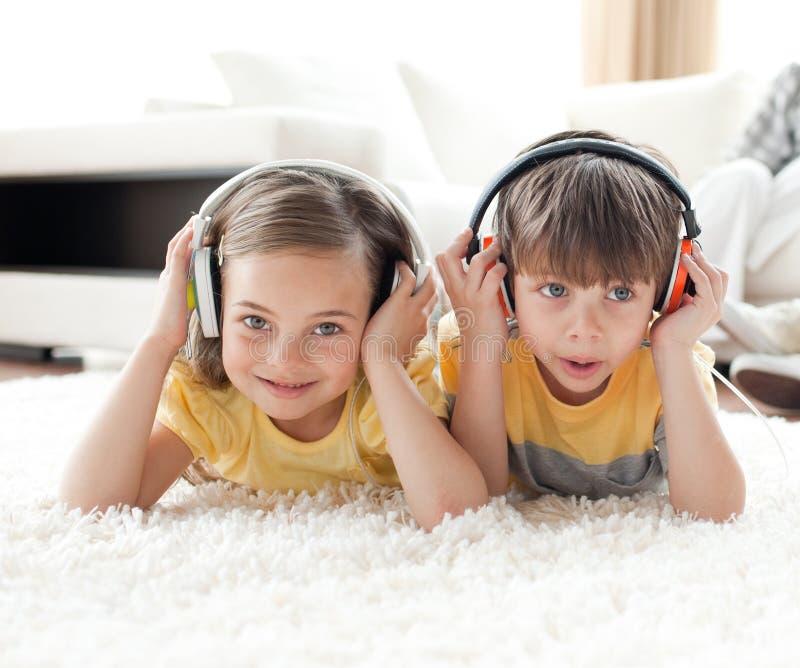 兄弟逗人喜爱的听的音乐姐妹 免版税库存图片