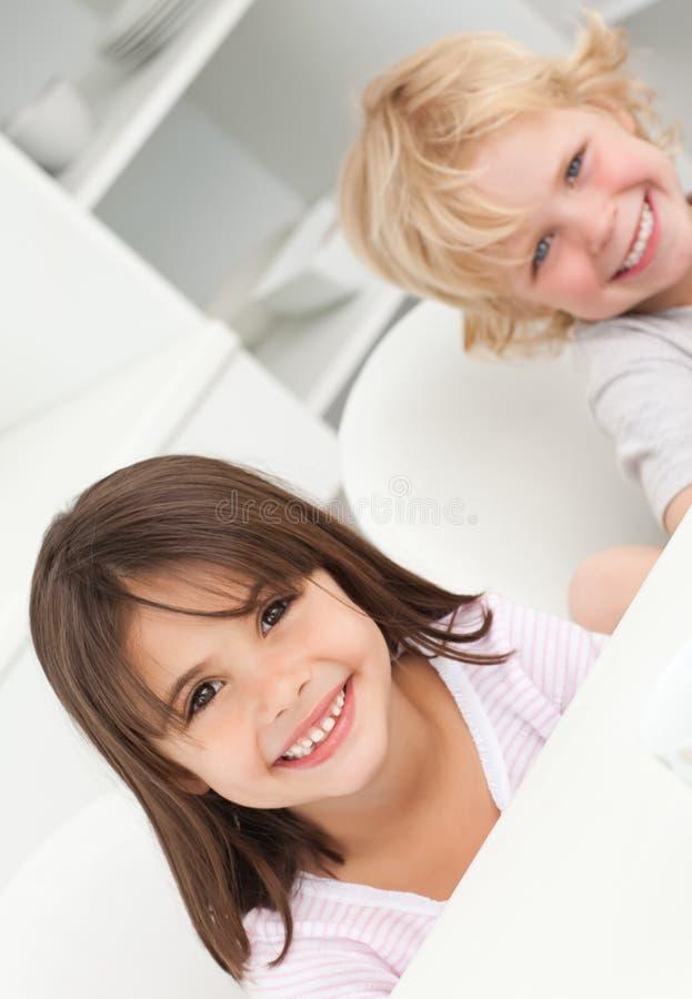 兄弟逗人喜爱的姐妹坐的表 免版税库存图片