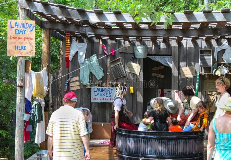 充分一个大罐子木盆水和妇女和徘徊在Renassiance节日马斯科吉OK的孩子有滑稽的标志的和洗衣店 免版税图库摄影