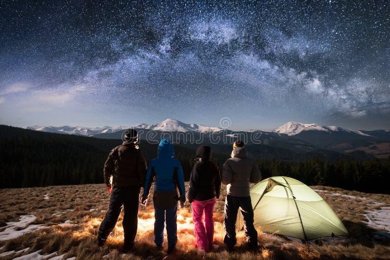 充分一起站立在阵营和帐篷旁边的四个人剪影在美丽的夜空下星和银河 图库摄影
