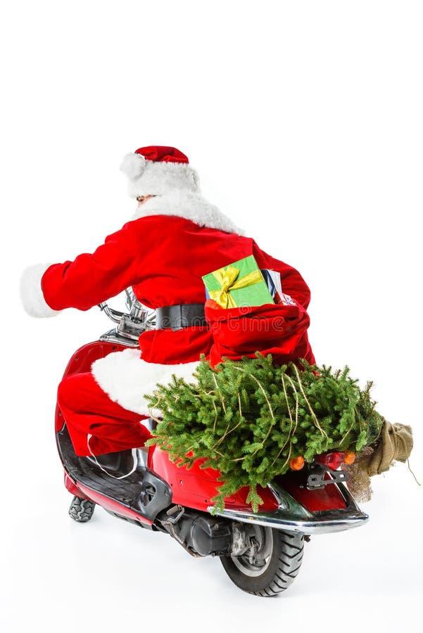 充分乘坐有圣诞树的红色滑行车和大袋子礼物的圣诞老人项目 免版税图库摄影