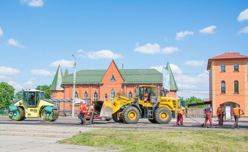 充分修理路的工作旅团使用履带牵引装置沥青摊铺机新鲜的沥青路面和压路机在夏天 工作者 免版税库存图片