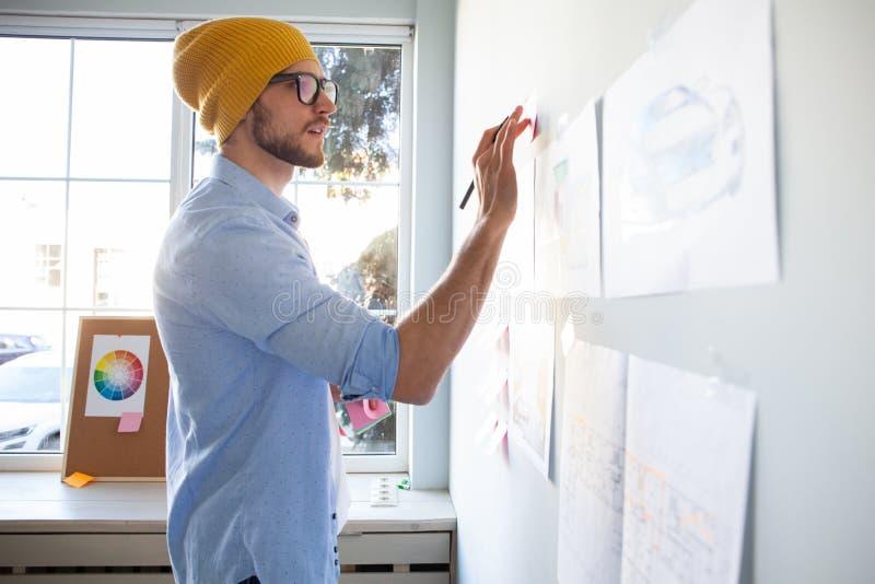充分写下想法的年轻创造性的人在墙壁稠粘的笔记 库存图片