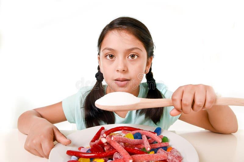充分吃盘糖果和gummies的哀伤和脆弱的西班牙女孩拿着在错误饮食概念的糖匙子 免版税库存照片