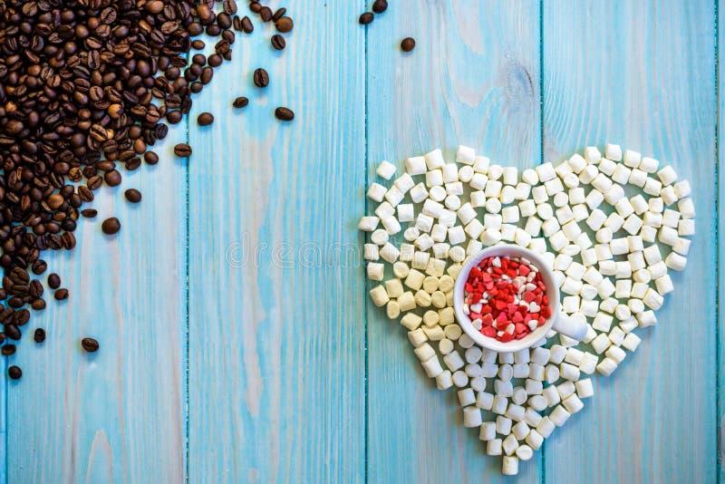 充分咖啡杯在土气浅兰的木背景的糖果平的位置 由蛋白软糖做的心脏形象 豆最左上侧 库存图片