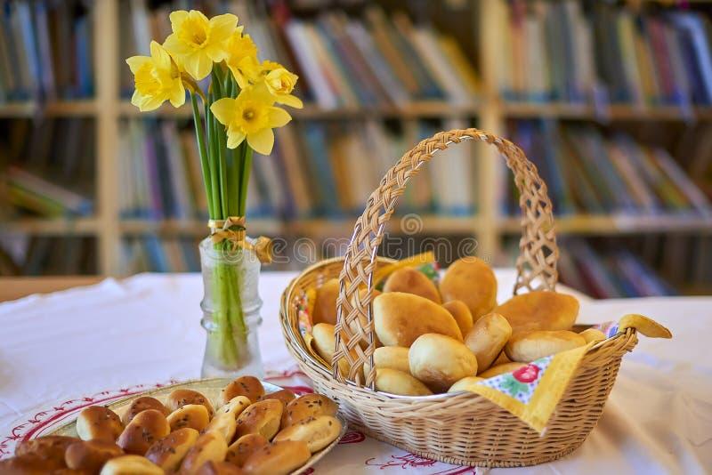 充分土气柳条筐和板材有批的被烘烤的物品,黄色黄水仙在玻璃花瓶,图书馆背景 免版税库存照片