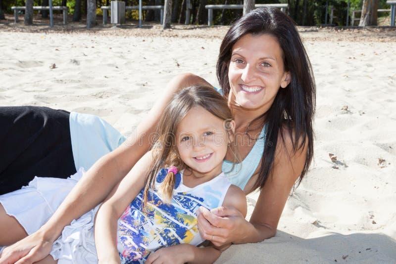 充分地一起说谎在与幸福爱的片刻、概念和联系的海滩的母亲和女儿在家庭 图库摄影