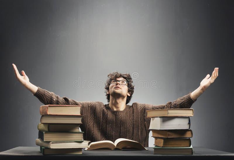充分坐在书桌的无能为力的年轻人书 图库摄影