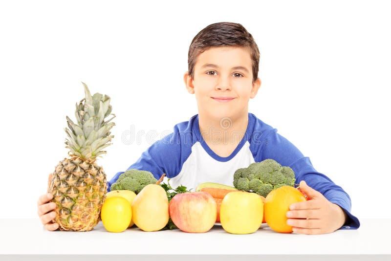 充分坐在桌上的微笑的男孩水果和蔬菜 图库摄影