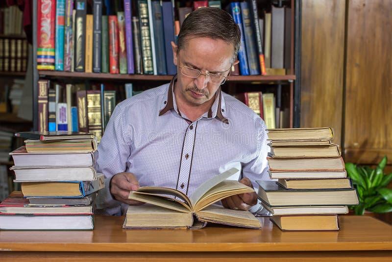 充分坐在他的书桌的资深商人书 免版税图库摄影