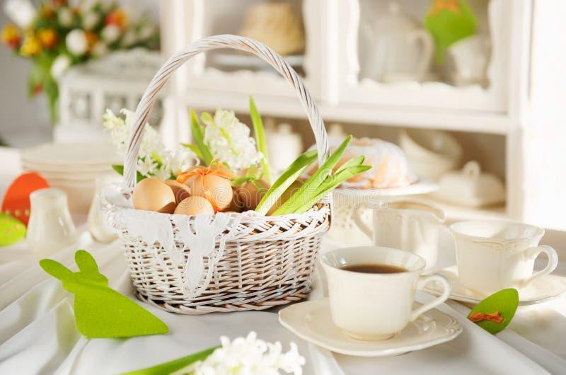 充分复活节篮子在一张欢乐桌上的鸡蛋 免版税库存图片