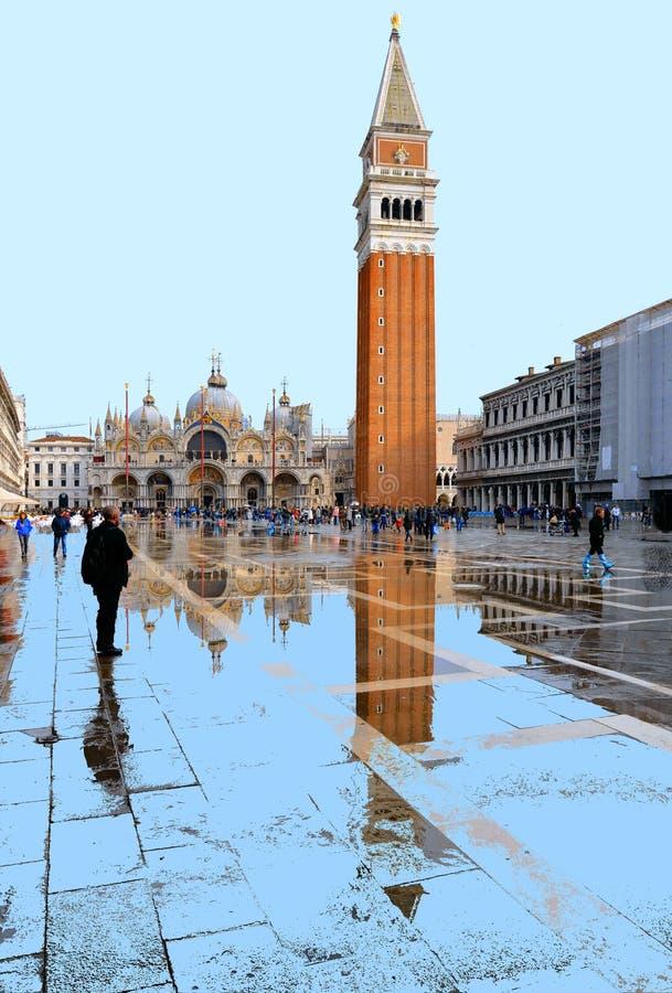充分威尼斯,意大利圣马克的广场在一次洪水期间的游人与钟楼的美好的水反射 库存照片