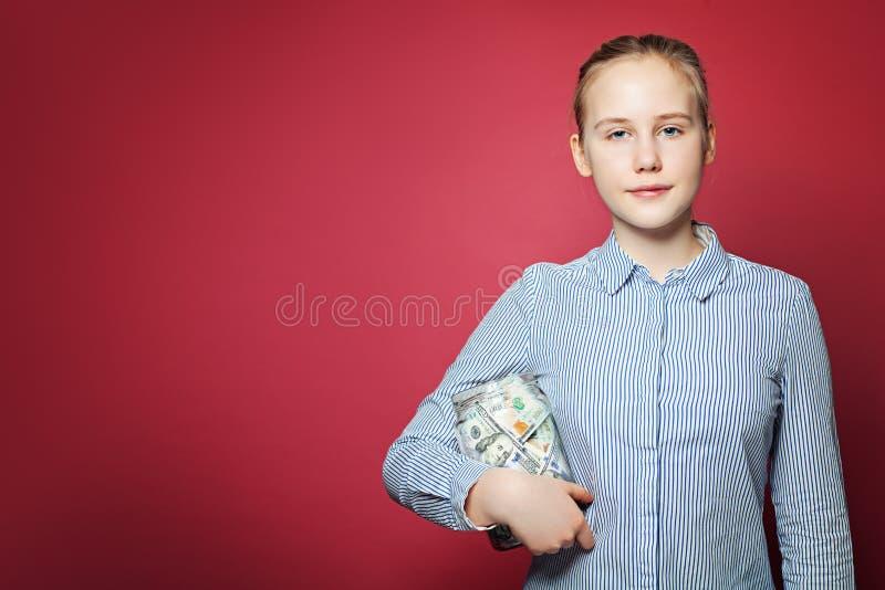 充分成功的青少年的女孩藏品瓶子在桃红色背景的金钱现金 免版税库存图片