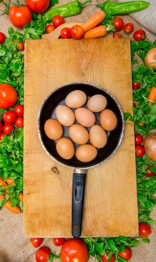 充分批评菜围拢的木表面上的鸡蛋-蔬菜沙拉、蕃茄、西红柿、红萝卜和意大利辣味香肠 图库摄影