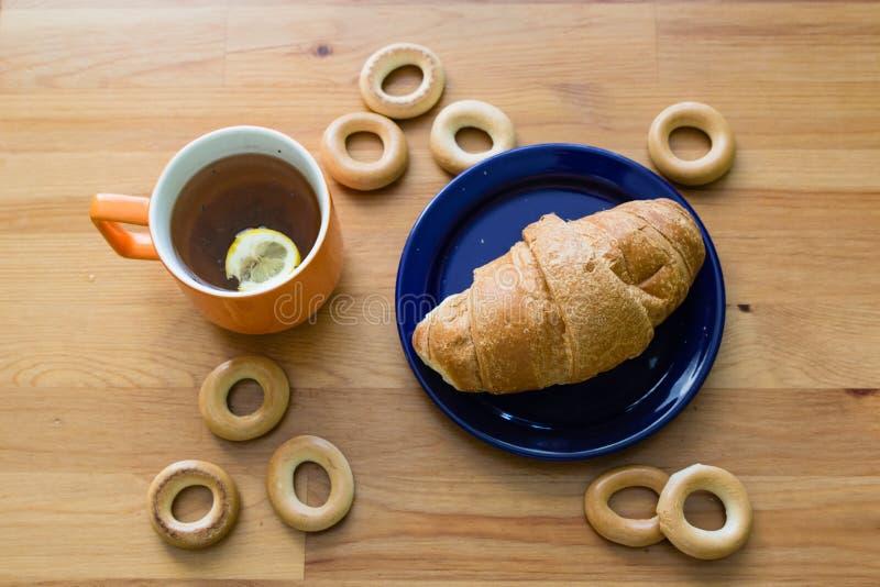 充分抢劫红茶用柠檬、新月形面包在板材和小百吉卷 免版税图库摄影
