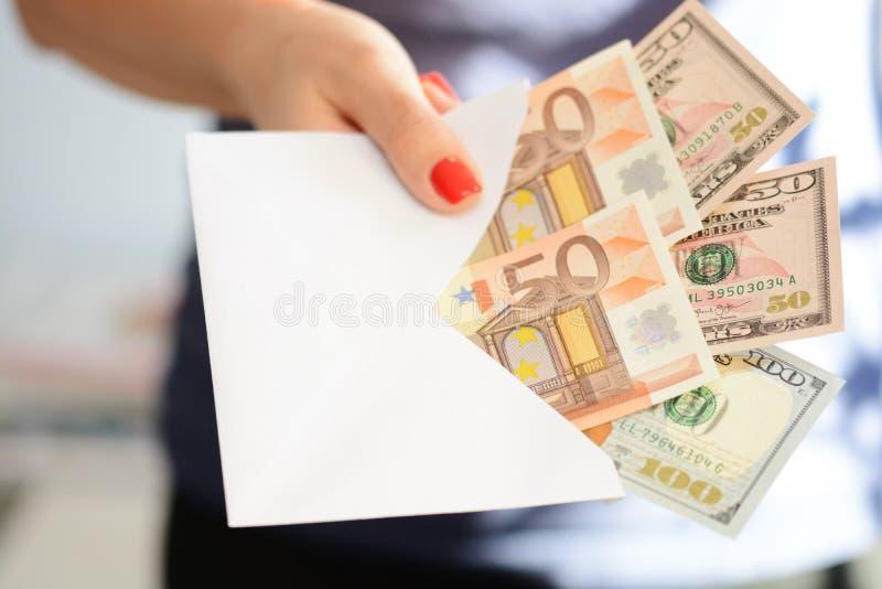 充分拿着和通过一个白色信封金钱的妇女手建议洗钱,非法现金调动和贿赂 免版税库存图片