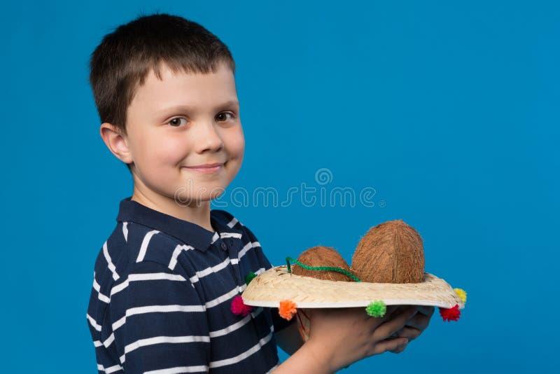充分拿着墨西哥帽旅行的椰子、概念和假期的微笑的男孩 免版税库存照片