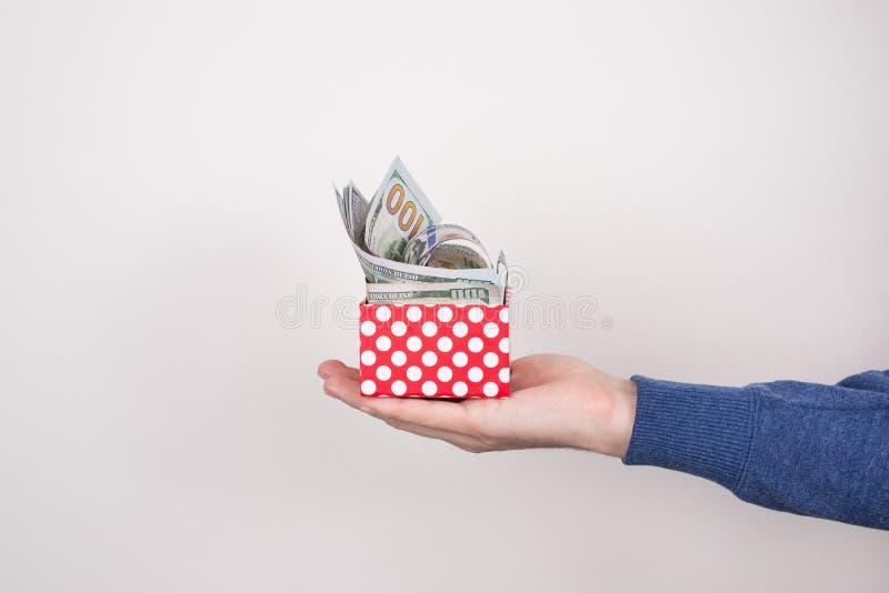 充分拿着小红色小的包裹金钱现金的手照片射击的播种的关闭落出于箱子被隔绝的灰色 库存图片