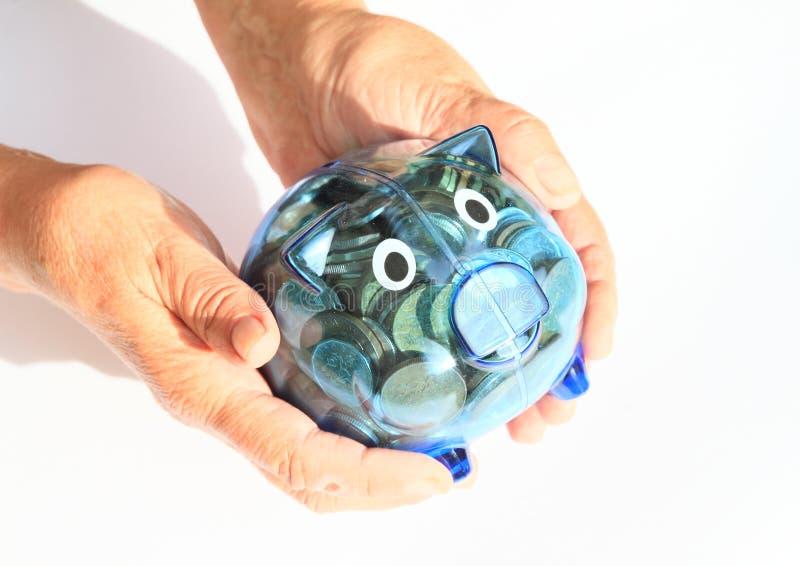 充分挽救猪金钱在手上 免版税库存照片
