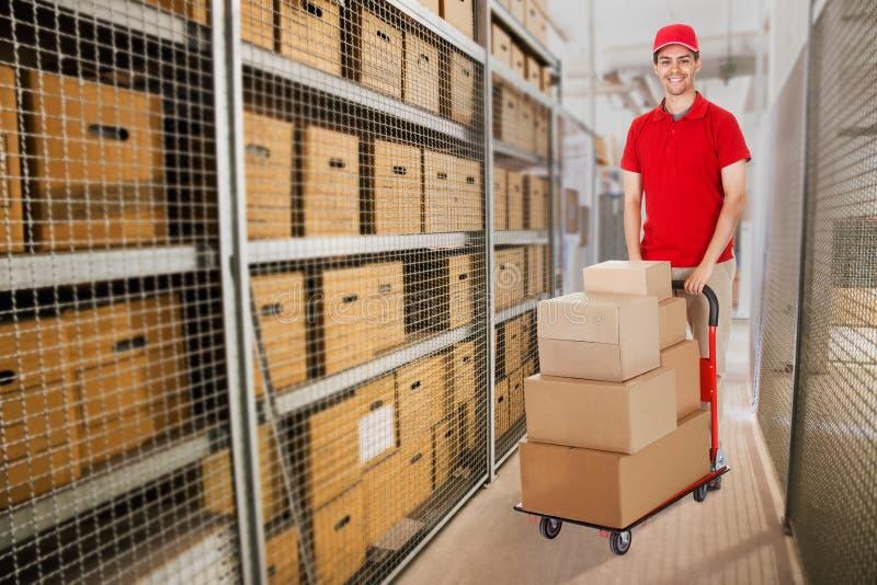 充分推挤推车箱子的送货人在仓库里 免版税库存照片