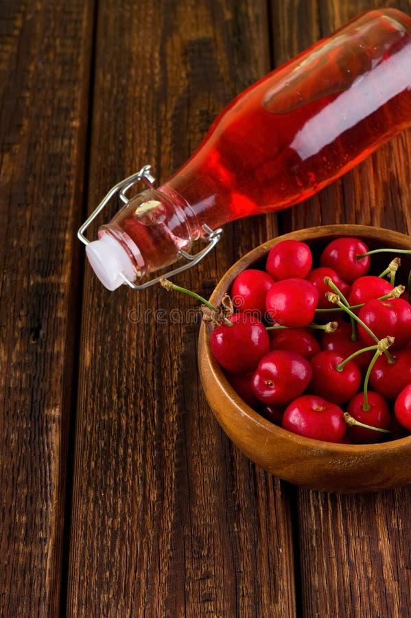 充分木碗樱桃和红色柠檬水 库存图片