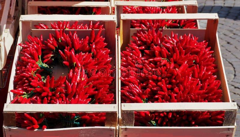 充分木箱束在太阳下的明亮的红辣椒在一个室外市场上 库存图片